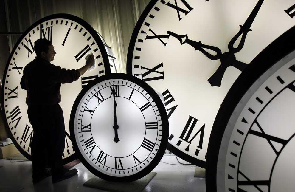 Walter Rodriguez, Angestellter bei Electric Time Co., reinigt das Zifferblatt einer über 2 Meter breiten Wegman-Uhr in einer Werkstatt in Medfield, Mass. Donnerstag, 30. 10. 2008. (Quelle: AP Photo/Elise Amendola)
